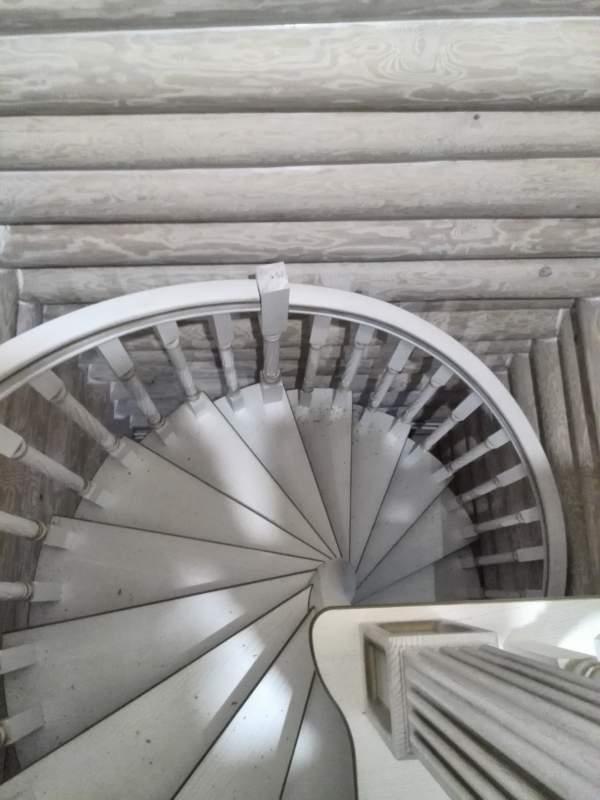 винтовая лестница в деревянном доме с гнутоклееным поручнем. Вид на лестницу сверху